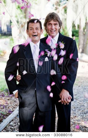 Gay wedding couple being showered with rose petals.