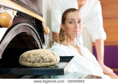 Man and woman in a bread sauna, the taste of fresh bread is activating the endorphins