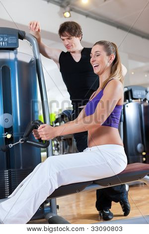 Young couple exercising in gym on different power machines to strengthen the muscles, the man is personal trainer