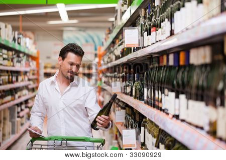 Young man looking at bottle of wine in supermarket