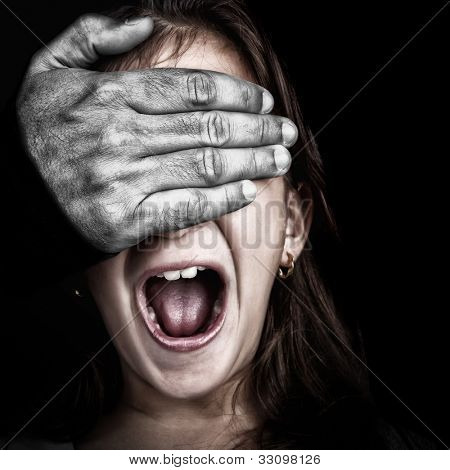 Close up of a girl being abused  by an adult  with a desaturated hairy hand covering her eyes while she screams