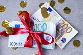 Euro Banknotes On A Stacks With Redgift Bow. Gift, Bonus Or Reward Concept. Selective Focus poster