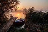 Morning Fog On The Lake With A Boat. Idyllic View From The Pier At Sunrise. poster