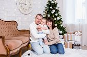 Christmas And Family Concept - Portrait Of Young Family With Cute Little Baby Girl Daughter Near Dec poster