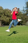 Active And Dynamic. Active Child Jump Over Green Grass. Happy Little Girl Move Active To Music. Ener poster