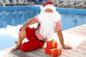 Authentic Santa Claus With Gift Boxes Near Pool At Resort poster