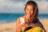 Happy young Asian woman using mobile phone texting online on beach vacation holiday travel summer li poster