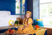 Little Girl Sitting On Work Surface Of Kitchen Waiting For Breakfast. Cheerful And Mischievous Girl  poster