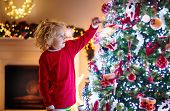 Child Decorating Christmas Tree. Kid On Xmas Eve. poster