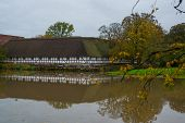 Egeskov Slot, Denmark, Europe: An Old Stable Building With Nice Reflection In A Pond Near Egeskov Ca poster