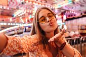 Photo of an cute pretty woman walking outdoors in amusement park take selfie by camera blowing kisse poster