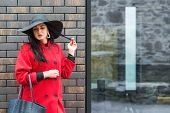 Gorgeous Fashionable Woman Walking On The Street. Girl Wearing Stylish Red Coat And Black Fashion Ha poster