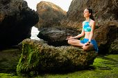 Yoga Lifestyle. Young Woman Meditating, Practicing Yoga And Pranayama At The Beach. Hands In Gyan Mu poster