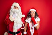 Middle age couple wearing Santa costume and glasses over isolated red background Looking fascinated  poster
