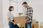 Satisfied Lovely Family Couple Carry Carton Box With Their Domestic Pet, Move In New Dwelling Prepar poster