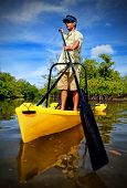 Man Paddling In Kayak For Fishing Excursion