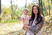 Lovely Mother And Child Walking In The Park. Mom With A Child In The Autumn On A Walk. Woman With Lo poster