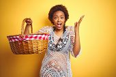 Young african american woman holding picnic basket on vacation over isolated yellow background very  poster