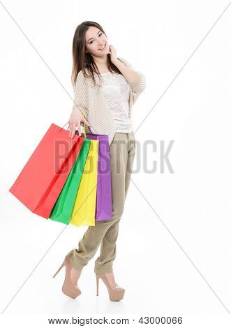 beautiful happy young woman with colored shopping bags, full length portrait of girl shopaholic over white