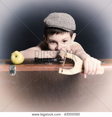 vintage art portrait of liitle boy looking at camera holding catapult and  leaning on old suitcase, retro stylization of 30-50s