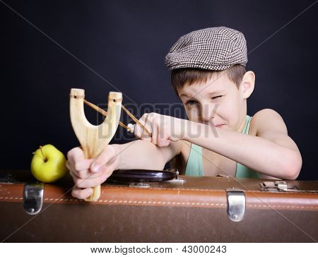vintage art portrait of little boy looking at camera fire a shot with catapult leaning on old suitcase, retro stylization of 30-50s