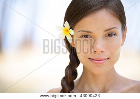 Woman natural beauty portrait of a beautiful and smiling brunette smiling outdoors with a flower in her braided hair. Multicultural Asian / Caucasian girl on health spa wellness travel resort