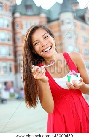 Woman eating ice cream in smiling happy in red summer dress in front of chateau frontenac in Quebec City, Quebec, Canada. Joyful multicultural Asian Caucasian tourist.