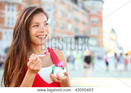 Happy tourist woman eating Ice cream in Quebec City in front of chateau frontenac in Quebec City, Quebec Canada. Smiling joyful mixed race Asian Caucasian girl enjoying holiday travel in summer dress