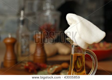 Whimsical still life of oil decanter 'wearing' a chef's hat.  Food preparation in rustic kitchen with stone fireplace as background.  Macro with shallow dof.  Cooking concept background image.