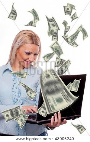 Attractive blonde holding laptop and american Dollar bills flying from screen - making money concept