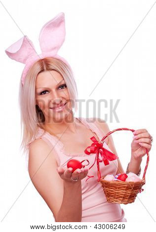 Lovely blonde with bunny ears holding in one hand red Easter egg and woven punnet with colorful eggs in the second hand