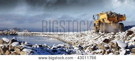 heavy truck driving in rough snowy terrain