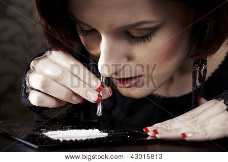 Beautiful woman snorting drugs