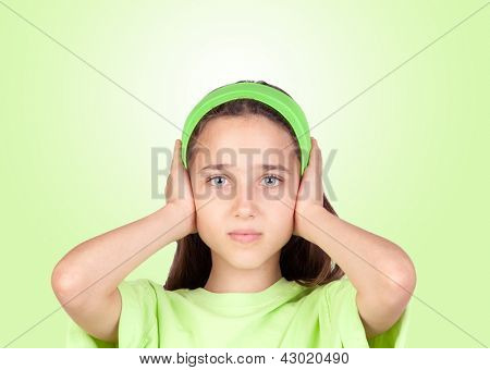 Frightened girl covering her ears isolated on a green background
