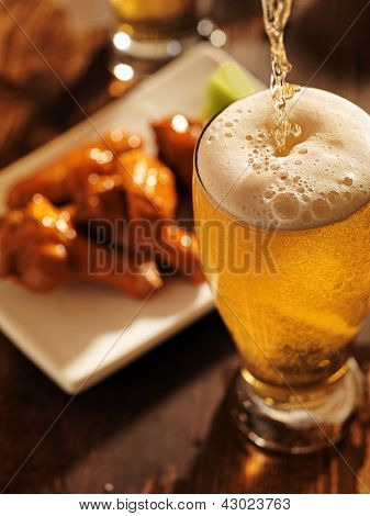 pouring beer with chicken wings in background.