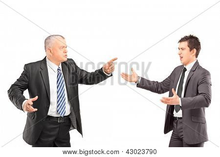 Mature man in a suit having a dispute with a young man in formal wear isolated on white background