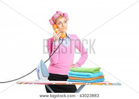 Beautiful young houswife with hair rollers and a telephone standing next to an ironing board