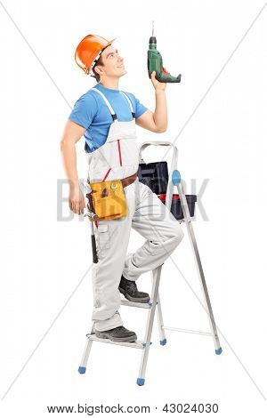 A young worker on a ladder holding a driller isolated on white background