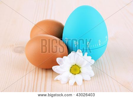 Blue egg timer and eggs, on wooden background