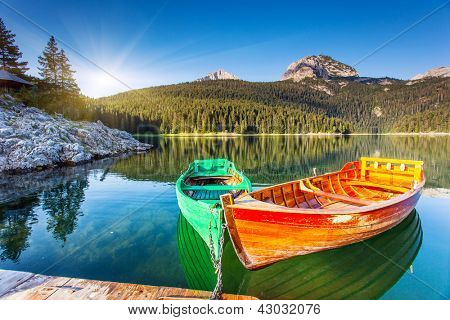Reflection in water of mountain lakes and boats. Black lake in Durmitor national park in Montenegro, Europe. Beauty world.