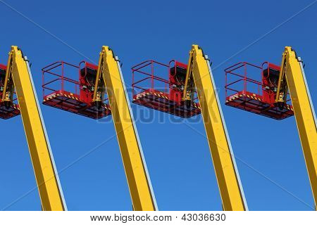 Cranes and hydraulic lifting platforms and a blue sky