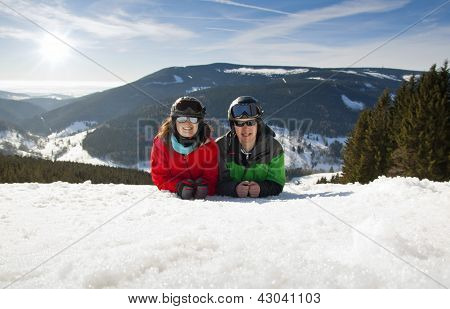 Young Happy Couple Lying In Snowy Mountains. Winter Sport Vacation