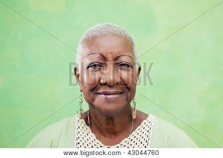 Portrait Of Senior Black Woman Smiling At Camera On Green Background