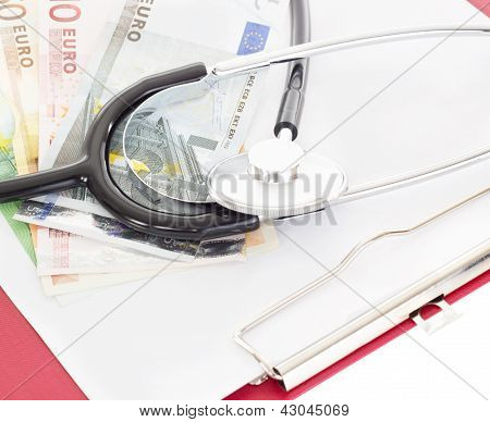 Money And Stethoscope On Clipboard