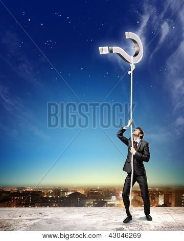 Image of businessman climbing rope attached to question sign aloft against city background