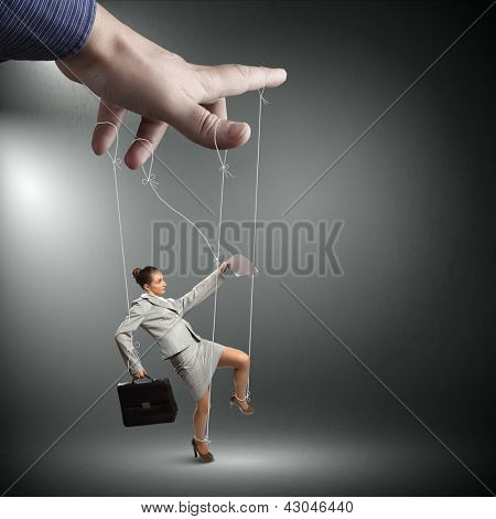 Businesswoman marionette on ropes with suitcase in hand