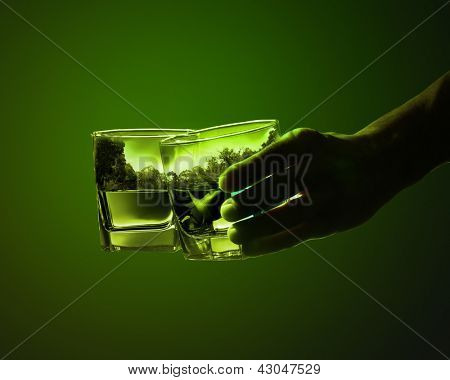 Two glasses of green absinth with nature illustration in
