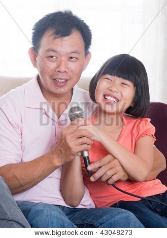 Happy Southeast Asian family living lifestyle. Portrait of a Asian father and daughter singing karaoke through microphone in the living room