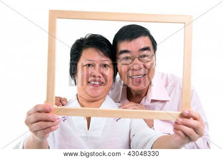 Smiling old Southeast Asian couple looking through an empty frame, isolated on white background
