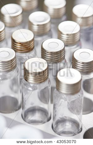 Close-up empty laboratory glass flasks in medicine cartridge. Shallow DOF